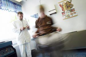 284 – Lääkärin vastaanotolla!  Sairaanhoitaja Jarmo Lehtimäki testaa asiakkaan matkapahoinvointia ja tasapainoelimiä. J.J. istuu rotaatiotuolissa.